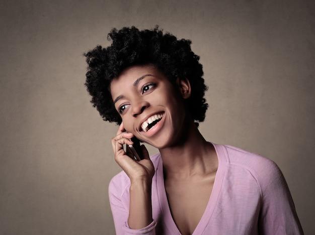 Portret młodej kobiety z krótkimi kręconymi włosami, rozmawiającej przez telefon i uśmiechniętej