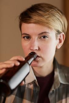Portret młodej kobiety z krótkimi włosami, picie piwa z butelki i patrząc na kamery