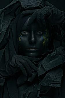 Portret młodej kobiety z malowaniem twarzy w czarnym tle