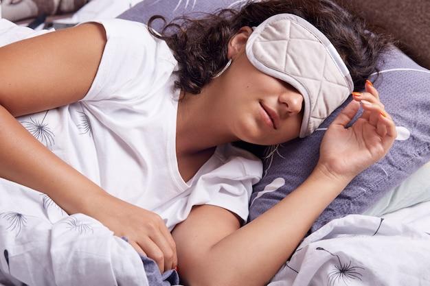 Portret młodej kobiety z maską do oczu śpiącą pod kocem, leżącej na poduszce, brunetki z falującymi włosami, sdorable lady ralaxing w domu