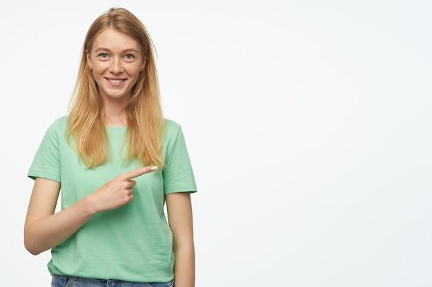 Portret młodej kobiety z piegami i długimi, zdrowymi blond włosami wskazuje z palcem wskazującym na bok w przestrzeń kopii, uśmiecha się szeroko