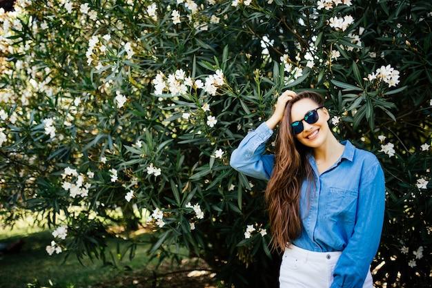 Portret młodej kobiety z piegami i kręconymi włosami, na tle letniego parku, zielonych liści. naturalne piękno.