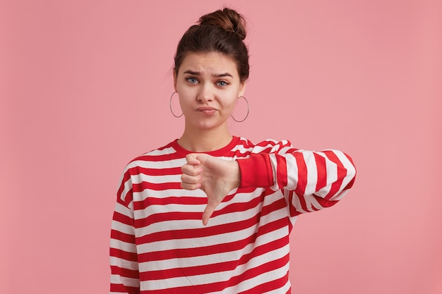 Portret młodej kobiety z piegami, nosi longsleeve w paski, patrzy na przód z niezadowoleniem, jest nastrojowa