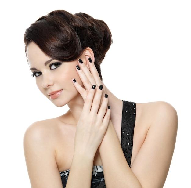 Portret młodej kobiety z pięknym czarnym manicure - na białym tle