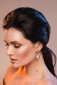 Portret młodej kobiety z pięknym makijażem i kolczykami z klejnotami na białym tle