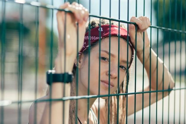 Portret młodej kobiety z poważnymi dredami marszcząc brwi, patrząc na ciebie przez ogrodzenie ogniwa łańcucha