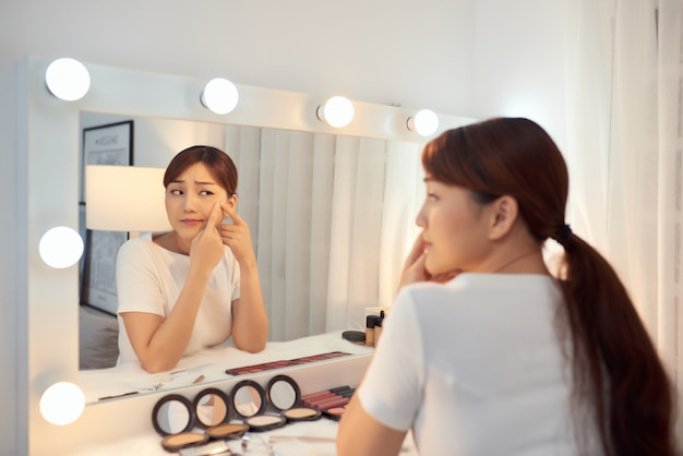 Portret młodej kobiety z problemem trądziku patrząc w lustro