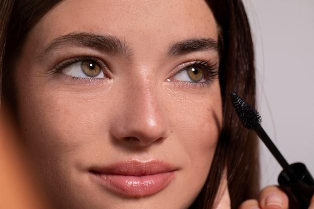 Portret młodej kobiety z produktem do makijażu