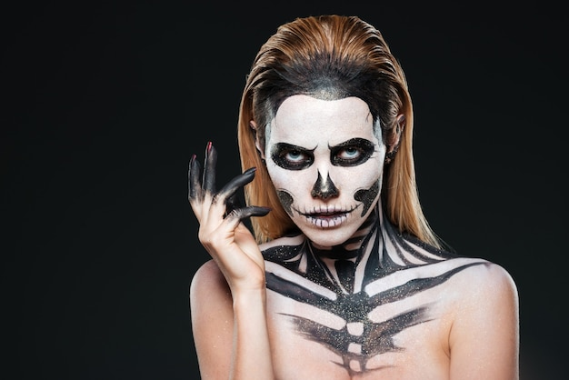Portret młodej kobiety z przestraszonym halloweenowym makijażem na czarnym tle