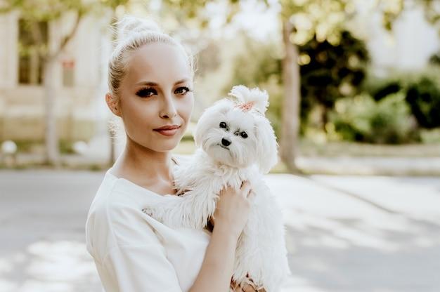 Portret młodej kobiety z psem maltańskim