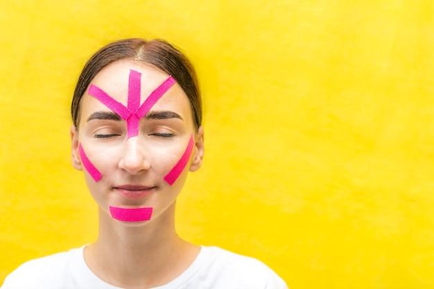 Portret młodej kobiety z taśmami kinesio na twarzy