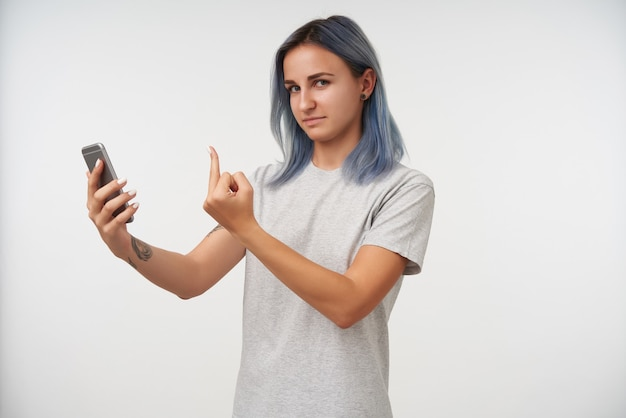 Portret młodej kobiety z tatuażem z krótkimi niebieskimi włosami, podnosząc rękę środkowym palcem podczas rozmowy wideo, stojąc na białym