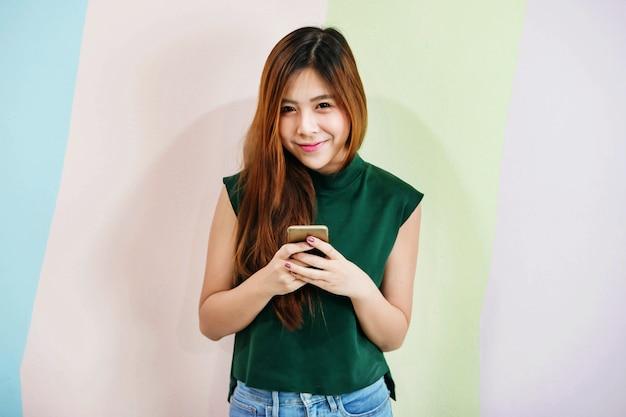 Portret młodej kobiety z uroczym uśmiechem podczas korzystania z inteligentnego telefonu