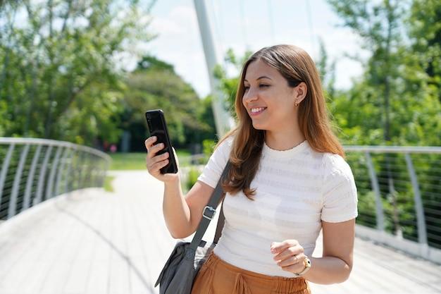 Portret młodej kobiety z wygodnymi ubraniami pisania palcem na telefonie komórkowym w parku miejskim. koncepcja technologii zrównoważonego, ekologicznego miasta i stylu życia.