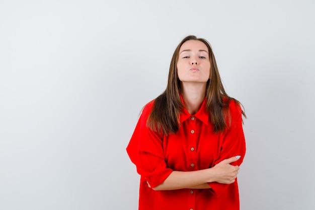 Portret młodej kobiety z założonymi rękoma, wydębionymi ustami w czerwonej bluzce i wyglądającym na spokojny widok z przodu