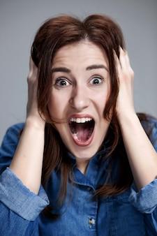 Portret młodej kobiety z zszokowanym wyrazem twarzy