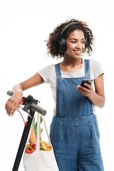 Portret młodej kobiety za pomocą słuchawek i telefonu komórkowego podczas jazdy na skuterze z torbą na żywność na białym tle nad białą ścianą