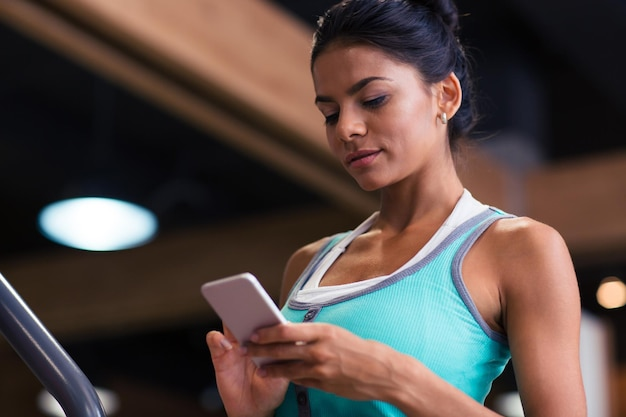 Portret młodej kobiety za pomocą smartfona w siłowni fitness
