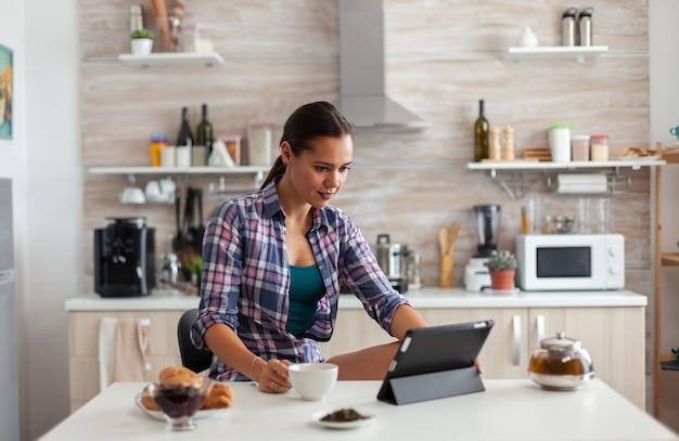 Portret młodej kobiety za pomocą tabletu rano, siedząc przy stole w kuchni, pijąc herbatę