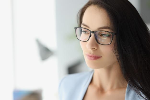 Portret młodej kobiety zamyślonej w okularach patrzącej przez okno