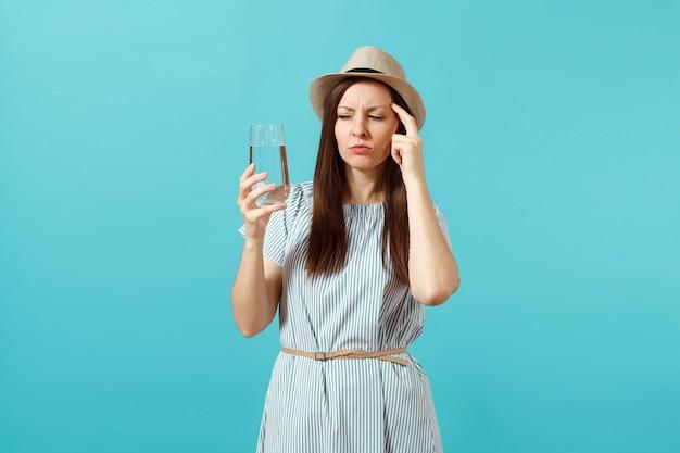 Portret młodej kobiety zamyślony w niebieskiej sukience, trzymając kapelusz i pijąc czystą świeżą czystą wodę ze szkła na białym tle na niebieskim tle. zdrowy styl życia, pojęcie szczere emocje ludzi. skopiuj miejsce.
