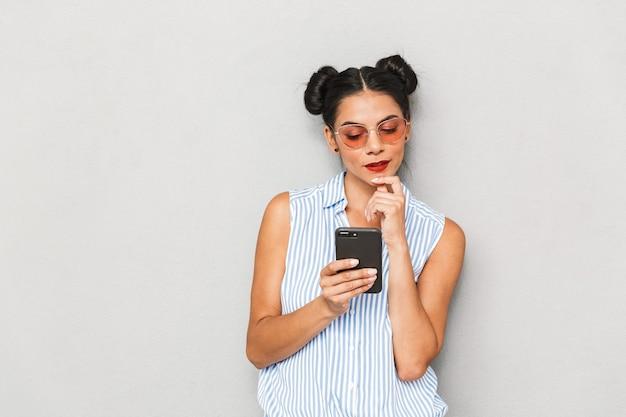 Portret młodej kobiety zamyślony w okulary na białym tle, przy użyciu telefonu komórkowego