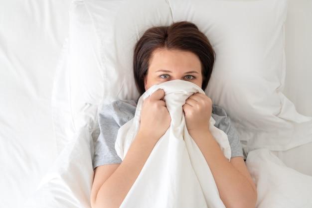 Portret młodej kobiety zaskoczony w łóżku