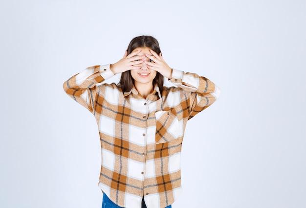 Portret młodej kobiety zasłaniając jej oczy na białej ścianie.