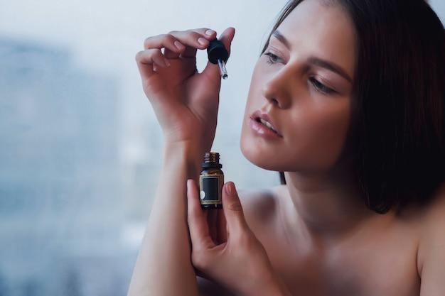 Portret młodej kobiety ze świeżą idealną skórą pozowanie w oknie z odbicia w szkle. koncepcja kosmetologii i leczenia. koncepcje reklamowe zdrowego stylu życia, spa i samoopieki. skopiuj miejsce