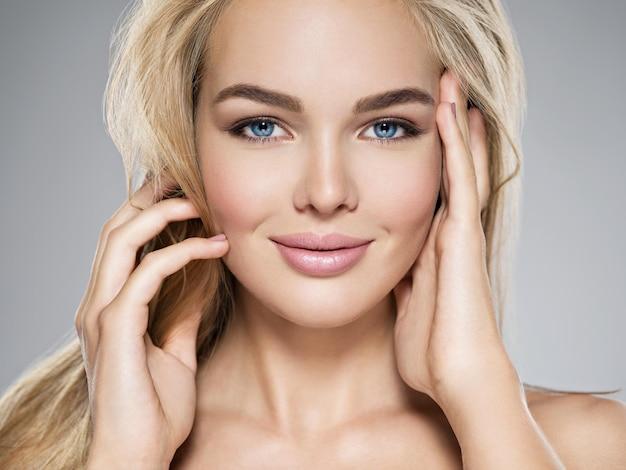 Portret młodej kobiety ze zdrową skórą twarzy. atrakcyjna suczka o długich, jasnych, prostych włosach i brązowym makijażu. całkiem cudowna dziewczyna o niebieskich oczach - pozowanie