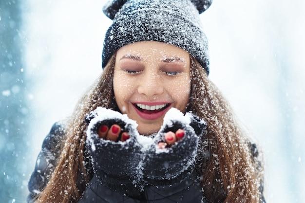 Portret młodej kobiety zima. piękna radosna modelka dziewczyna śmieje się i dobrze się bawi w winter park