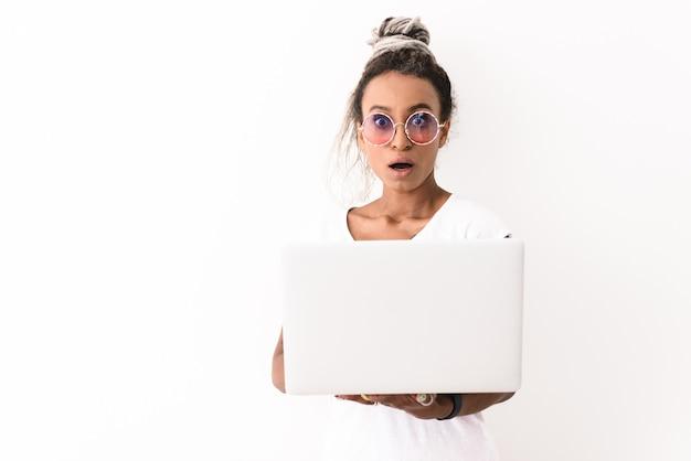 Portret młodej kobiety zszokowany emocjonalny z dreads stwarzających na białym tle na białym przy użyciu komputera przenośnego.