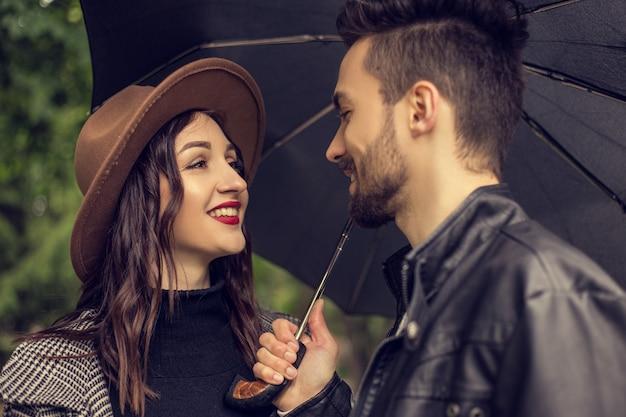 Portret młodej kochającej się pary spacerującej po parku miejskim i chroniącej przed deszczem parasolem kochankowie heteroseksualni spotykają się na randce, spędzając razem czas w pochmurny, deszczowy dzień, okazując emocje