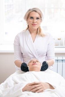 Portret młodej kosmetyczki w czarnych rękawiczkach przy użyciu wacika do czyszczenia skóry twarzy dojrzałej kobiety przed zabiegiem