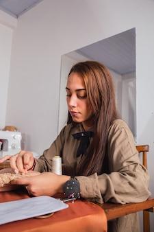 Portret młodej krawcowej kobiety do szycia skoncentrowanej w swoim warsztacie.
