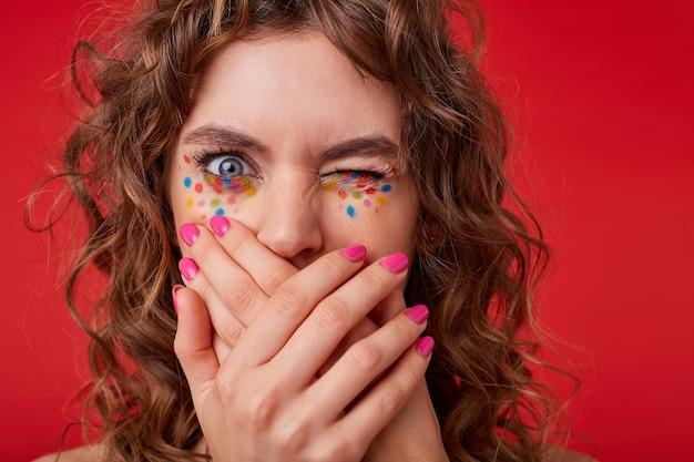 Portret młodej kręconej kobiety ze skrzyżowanymi dłońmi na ustach, patrząca jednym zamkniętym okiem, stojąca, okazująca obrzydzenie, zdezorientowana