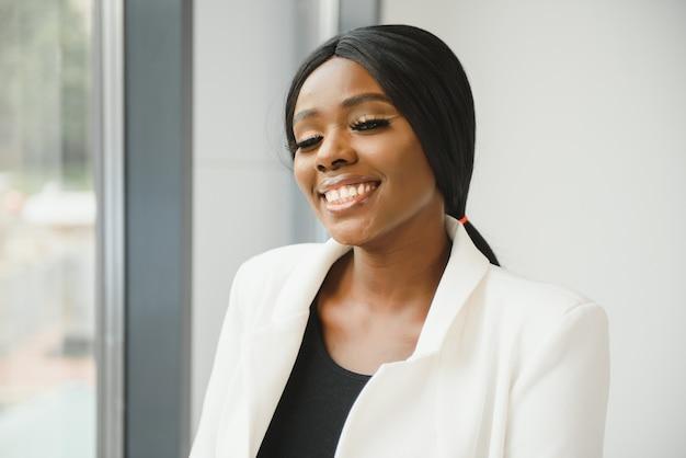 Portret młodej ładnej afroamerykańskiej bizneswoman w biurze