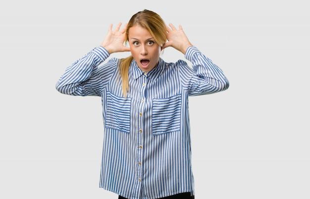 Portret młodej ładnej blondynki kobiety szalony i desperacki, krzyczący z kontrola