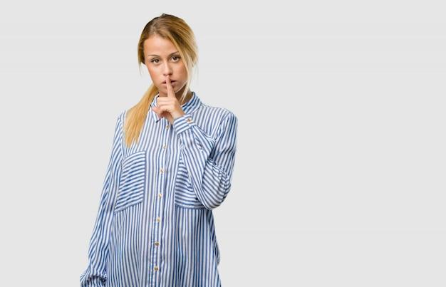 Portret młodej ładnej blondynki kobiety utrzymującej sekret lub proszącej o ciszę, poważną twarz