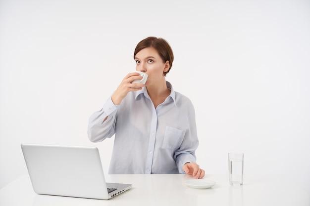 Portret młodej ładnej brunetki kobiety z krótką modną fryzurą pijącą kawę podczas przerwy w pracy, siedzącą przy stole na białym tle z nowoczesnym laptopem