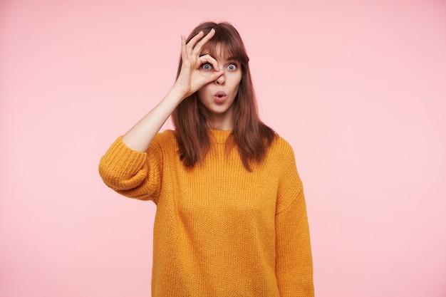 Portret młodej, ładnej brunetki z otwartymi oczami, która wygląda zdziwiona i trzyma podniesioną rękę blisko oka, składając usta, pozując na różowej ścianie