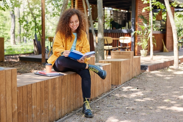 Portret młodej, ładnej ciemnoskórej, kręconej studentki siedzącej na tarasie kawiarni, ubrana w żółty fartuch, pijąca kawę i szeroko uśmiechnięta, lubi się uczyć, przygotowywać do egzaminów.