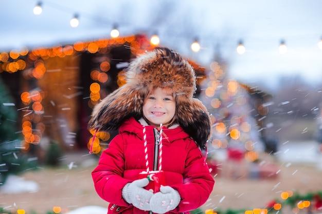 Portret młodej ładnej dziewczyny w tradycyjnej rosyjskiej czapce futrzanej z nausznikami i czerwoną kurtką zimową z filiżanką kakao na tle bożego narodzenia.