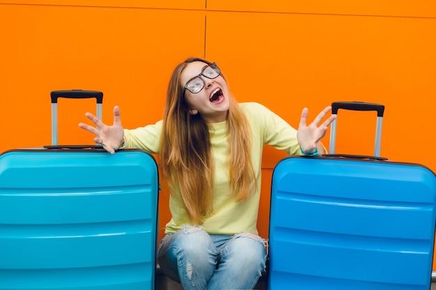 Portret młodej ładnej dziewczyny z długimi włosami w czarnych okularach siedzi na pomarańczowym tle między dwiema walizkami. ma długie włosy i żółty sweter. ona śmieje się.