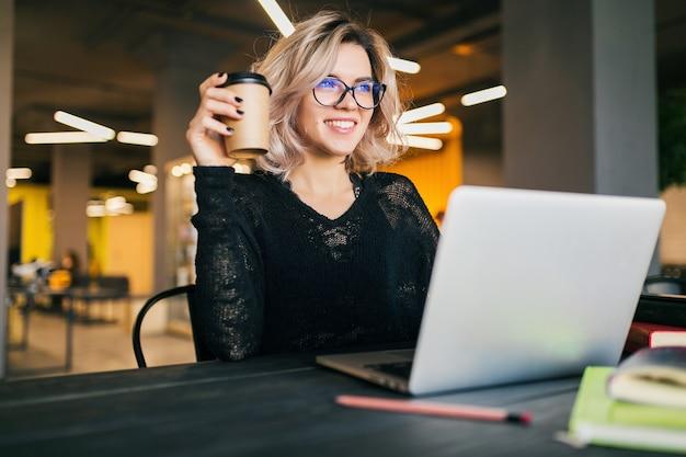 Portret młodej ładnej kobiety siedzącej przy stole w czarnej koszuli pracy na laptopie w biurze współpracującym