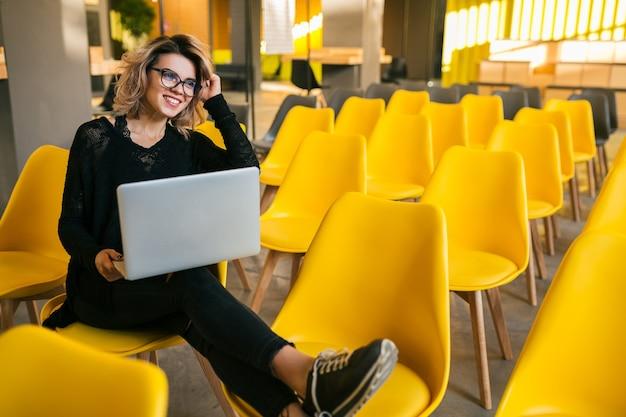 Portret młodej ładnej kobiety siedzącej w sali wykładowej, pracującej na laptopie, w okularach
