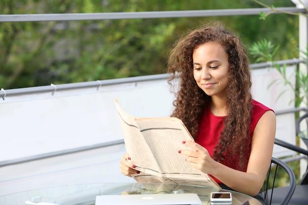Portret młodej ładnej kobiety w czerwonej sukience czytania gazety na letnim tarasie