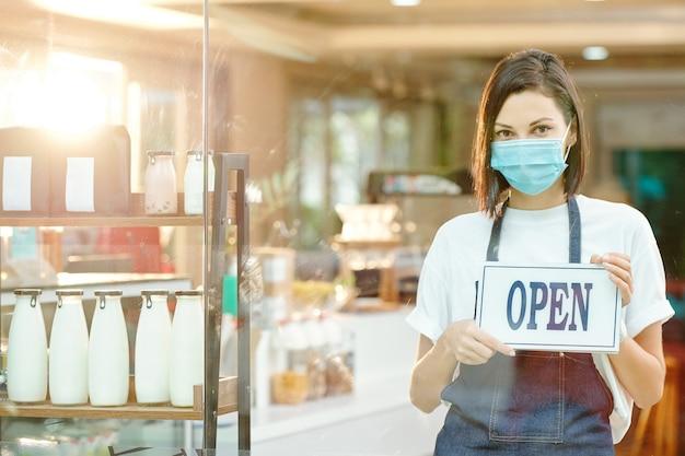 Portret młodej ładnej kobiety w masce ochronnej stojącej przy półce z butelką mleka i jogurtu w sklepie i trzymającej otwarty znak