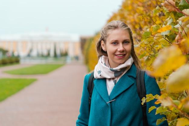 Portret młodej, ładnej kobiety z uśmiechem pozuje obok płotu z żółtych liści.