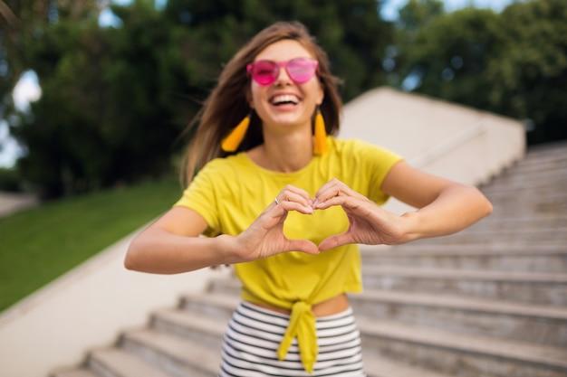 Portret młodej, ładnej uśmiechniętej kobiety bawiącej się w parku miejskim, pozytywna, emocjonalna, ubrana w żółty top, kolczyki, różowe okulary przeciwsłoneczne, trend w modzie na lato, stylowe akcesoria, pokazujący znak serca